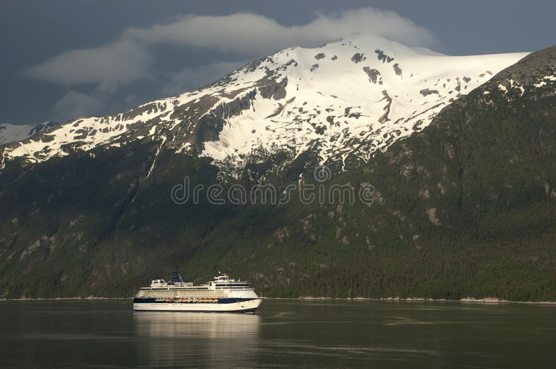 Cruise ship crusing Fjord in Alaska Inside Passage royalty free stock image