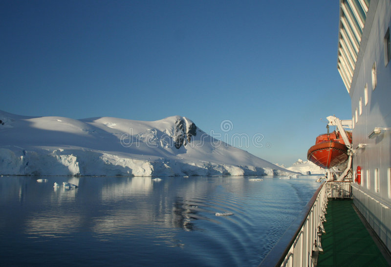 Cruise ship with lifeboat, mountains & glaciers reflected in calm ocean, stock image