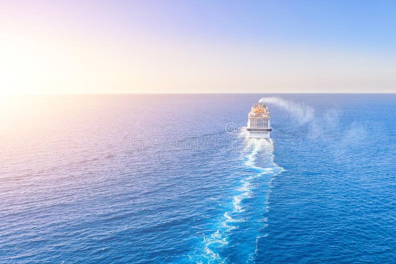 Cruise ship liner goes into horizon the blue sea leaving a plume on the surface of the water seascape during sunset. Aerial view, royalty free stock images