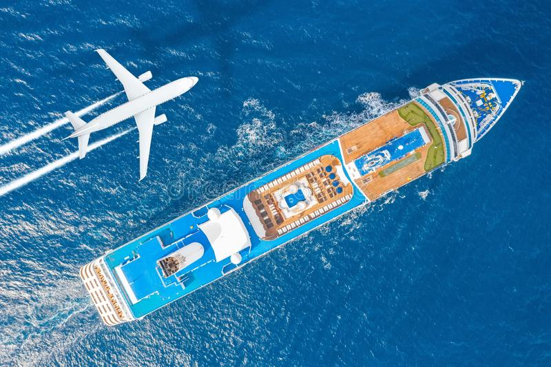 Cruise ship liner sails in the blue sea leaving a plume on the surface of the water seascape, and flying airplane with a trail of royalty free stock photo