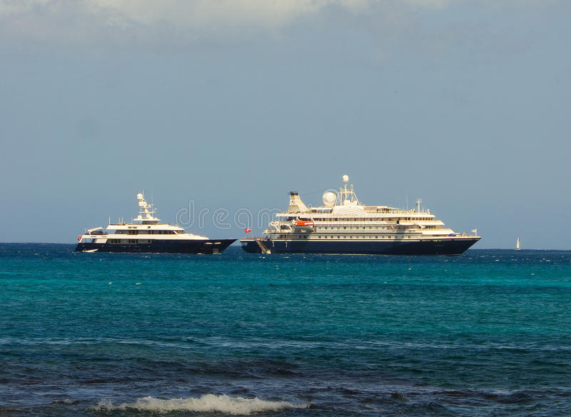 A cruise ship and luxury poweryacht at admiralty bay, bequia stock photography