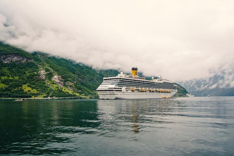 Cruise ship in norwegian fjord. Passenger liner docked in port. Travel destination, tourism. Adventure, discovery. Geiranger, Norway - January 25, 2010: cruise royalty free stock photo