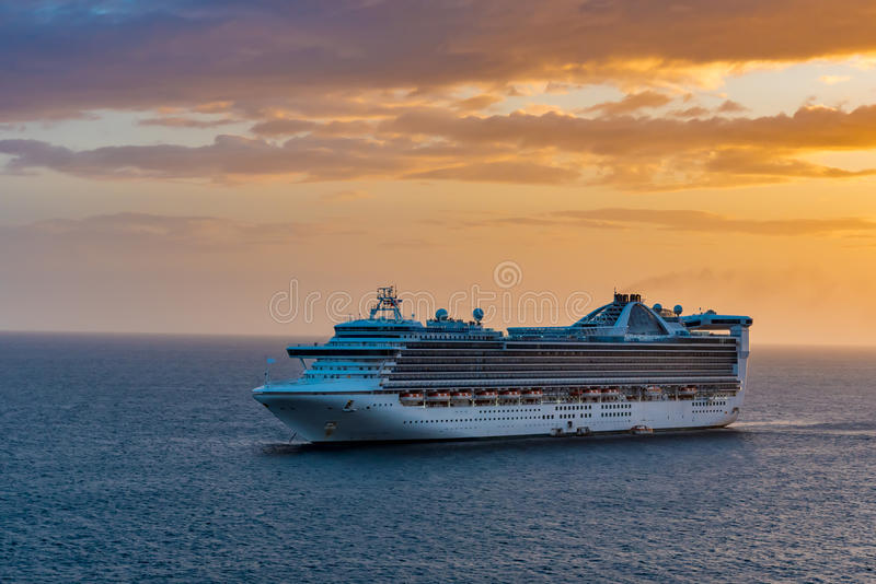Cruise Ship on the Ocean at Sunset. Cruise Ship on the Ocean at orange sunset stock photo