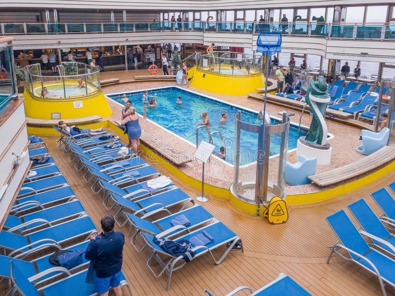 Cruise ship passengers have fun in the swimming pool on the upper deck royalty free stock images