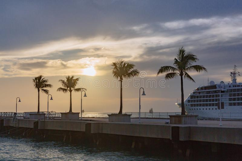 Cruise ship by a pier with palm trees at sunset, in Key West, Fl royalty free stock photos