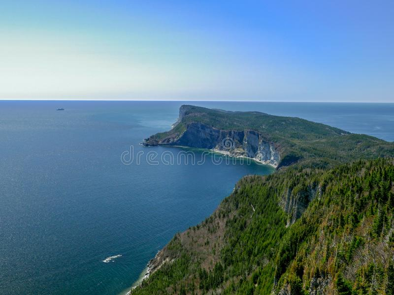 Cruise ship rounding the majestic Cape Gaspe in Forillon National Park, Canada. Cruise ship, far on the horizon, rounding the majestic Cape Gaspe in Forillon stock photo