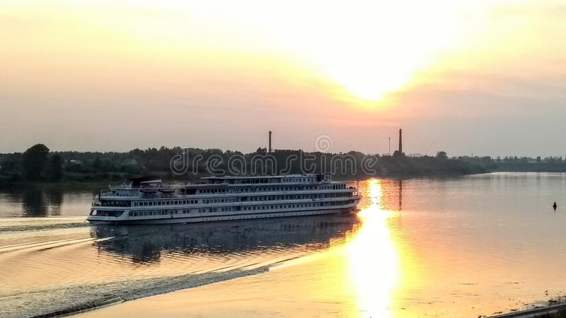 Cruise ship running to the west at sunset photo landscape. Cruise ship running along the Volga river to the west at sunset photo landscape stock photo