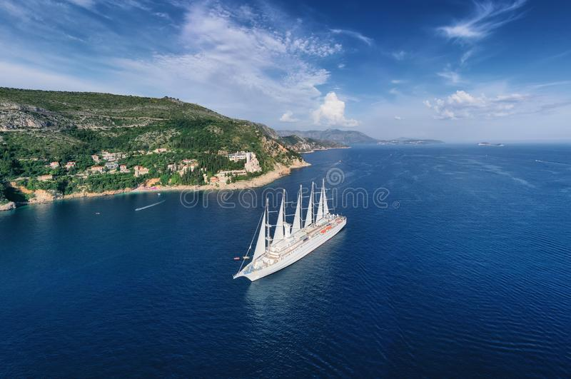 Cruise ship with sail from top view. Blue sea water background from top view. Summer seascape from air. royalty free stock photography