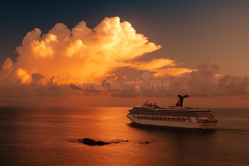 Cruise ship sailing in the sunset with white clouds over the Caribbean sea. stock photo