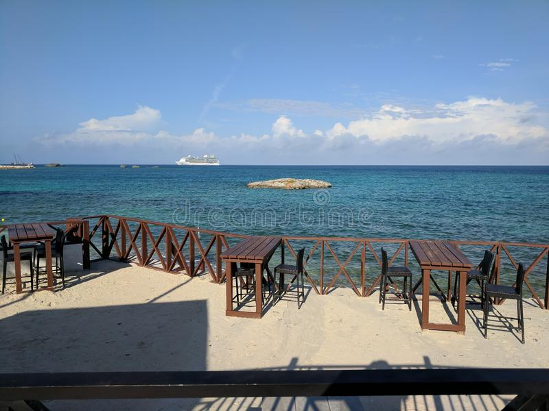 Cruise ship seen from empty beach bar cafe. In the Bahamas, with small island offshore stock photos