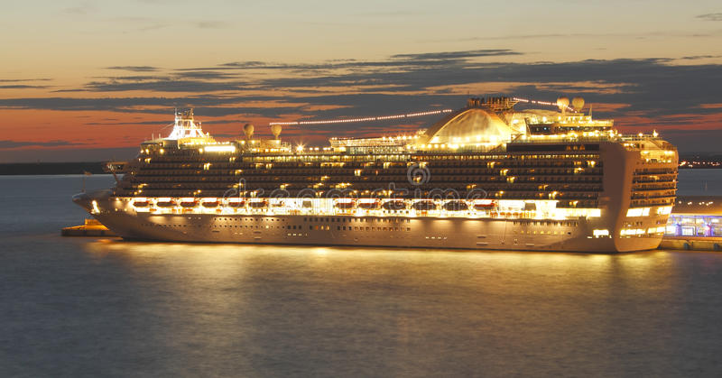 Cruise ship sunset. Cruise ship all lit up at sunset royalty free stock image