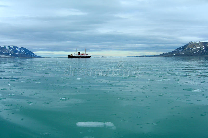 Cruise ship on Svalbard. Cruise ship in evening light in a fjord on Spitsbergen, Svalbard royalty free stock images