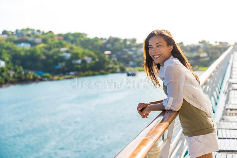 Cruise ship vacation Asian woman relaxing on deck enjoying view from boat of port of call city on St. Lucia island in the stock photos