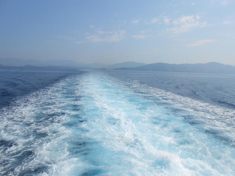 Cruise ship wake. Photography of cruise ship wake, blue water and sky.Wake behind boat underway. Wake from the back of a cruise ship stock image