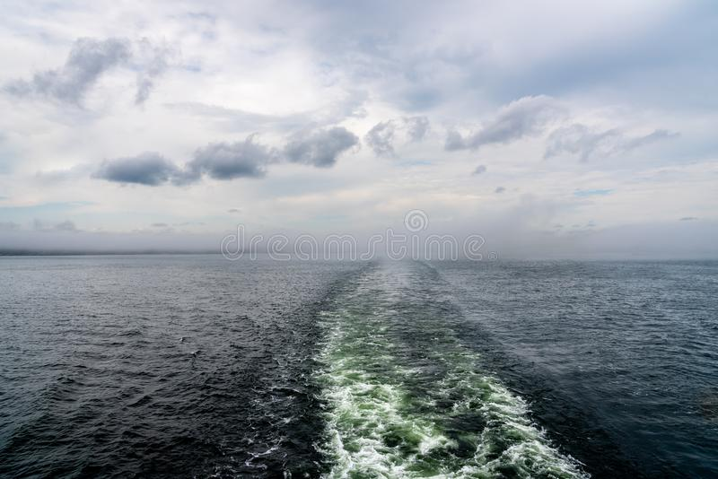 Cruise ship wake trail against hazy horizon with clouds. Horizontal composition royalty free stock photos