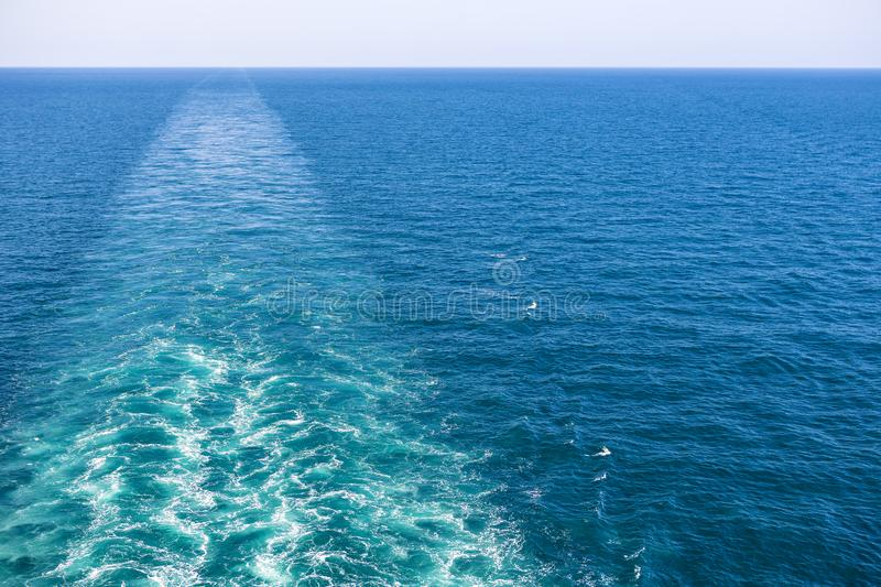 Cruise ship wake or trail on ocean surface, white trace. Cruise ship wake on the sea surface, ocean boat foam trail royalty free stock images