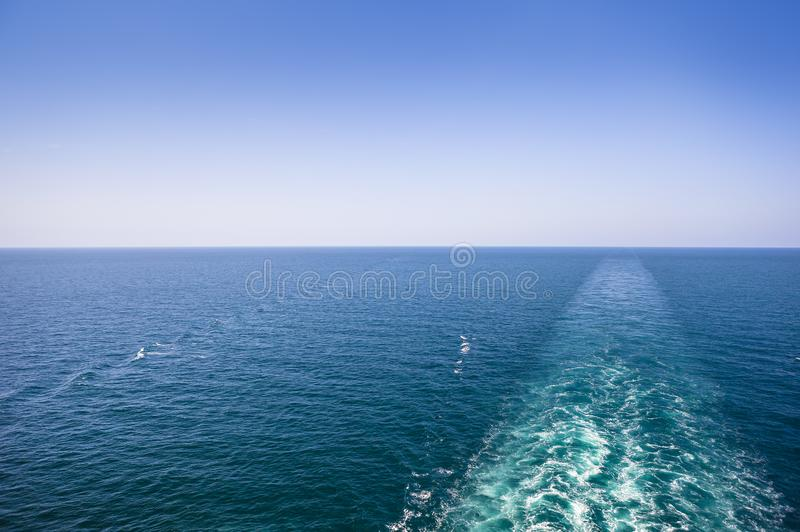 Cruise ship wake or trail on ocean surface, white trace. Cruise ship wake on the sea surface, ocean boat foam trail stock image
