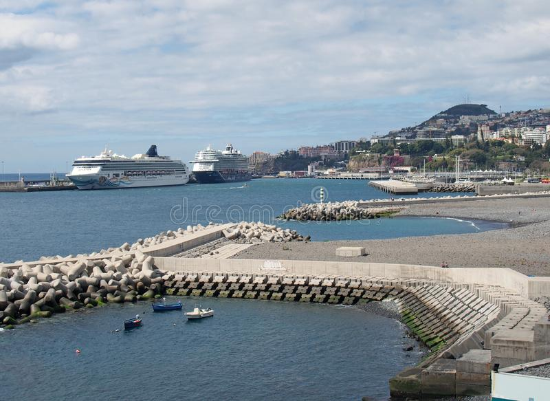cruise ships moored in the harbour area of funchal in madeira next to the city with smaller fishing boats near the concrete jetty royalty free stock photo