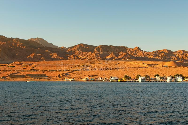 Cruise ships moored in the port in Dahab. Scenic landscape of Red Sea with beautiful coastline and mountains at the background. royalty free stock image