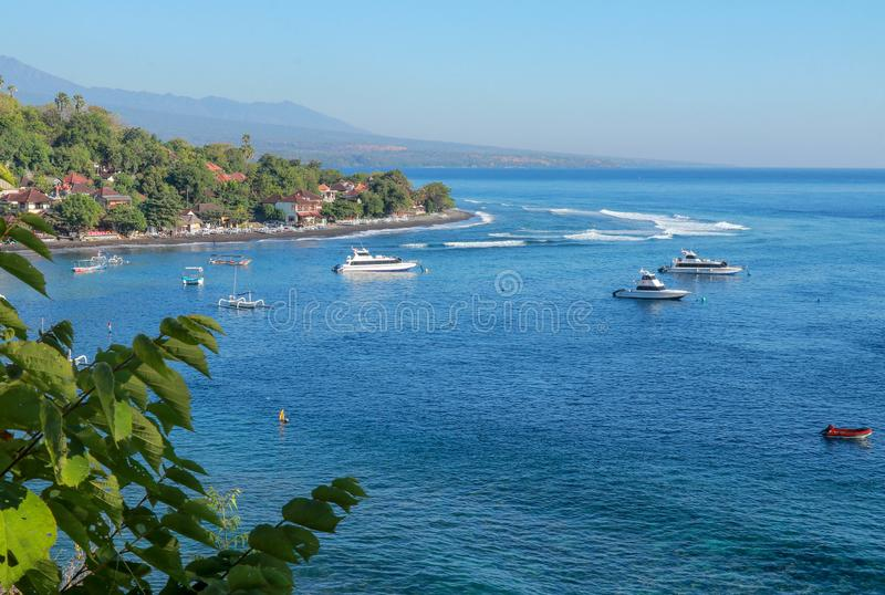 Cruise ships and traditional fishing boats anchored in the safety of Bali Bay in Indonesia. The waves hit the coral barrier. stock images