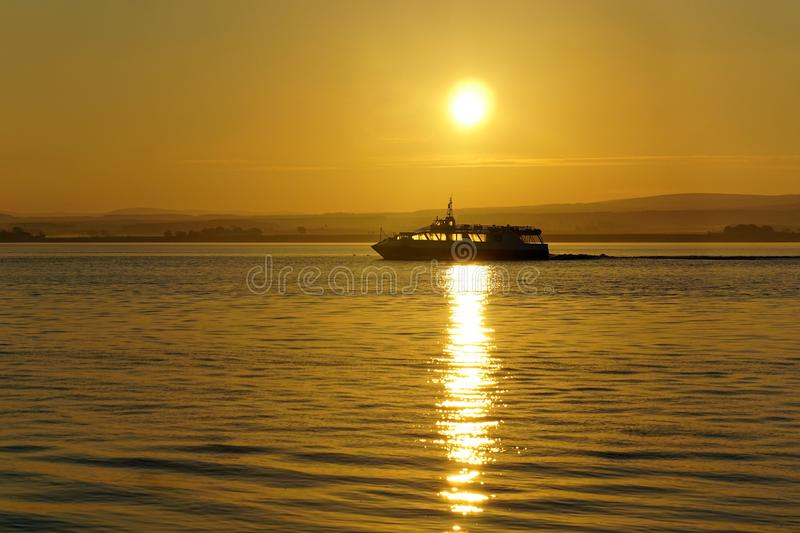 Cruise at sunrise on ther Moray Firth. A boat cruises in a misty sunrise on the Moray Firth near the Black Isle in Scotland stock images