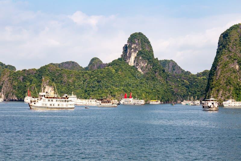 Cruiseboten die onder de karst vormingen in Halong-Baai, Vietnam, in de golf van Tonkin varen stock foto's