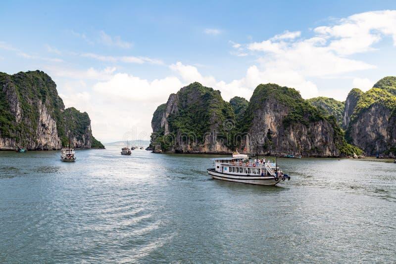 Cruiseboten die onder de karst vormingen in Halong-Baai, Vietnam, in de golf van Tonkin varen royalty-vrije stock fotografie