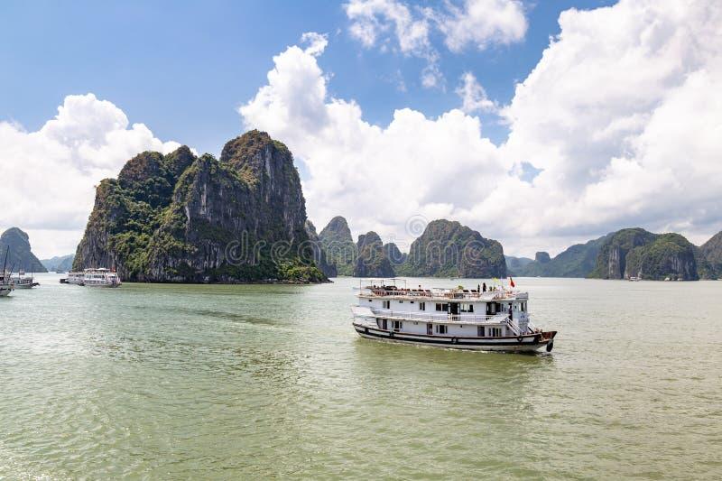 Cruiseboten die onder de karst vormingen in Halong-Baai, Vietnam, in de golf van Tonkin varen royalty-vrije stock afbeelding