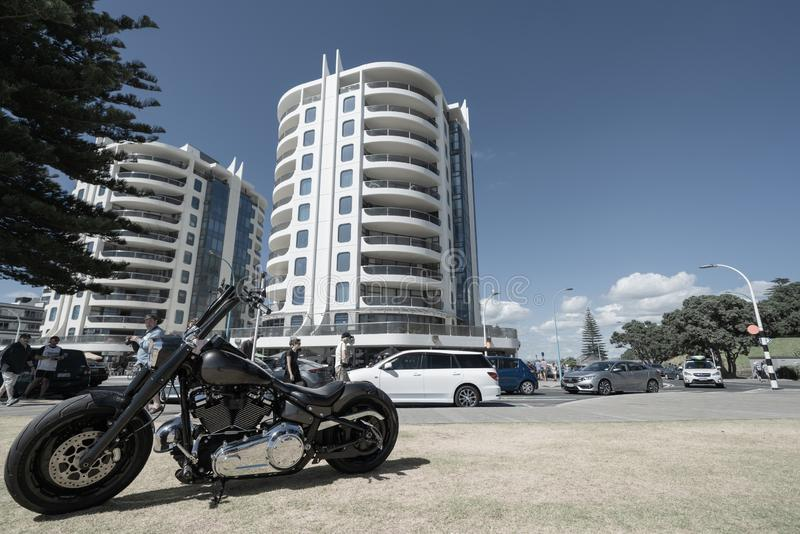Cruiser motorbike parked on berm at Mount MAin Beach with Oceanscide twin Towers background. MOUNT MAUNGANUI NEW ZEALAND - FEBRUARY 10 2019: Cruiser motorbike royalty free stock image