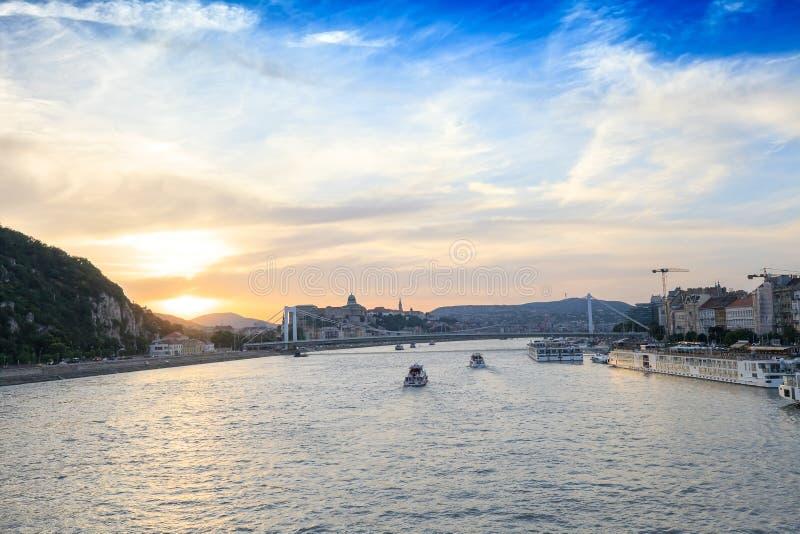 Cruiseschepen op de rivier van Donau bij zonsondergang in Boedapest, Hongarije royalty-vrije stock afbeelding