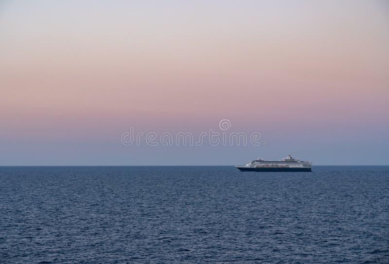 Cruiseschip die het overzees varen bij zonsopgang of dageraad stock foto