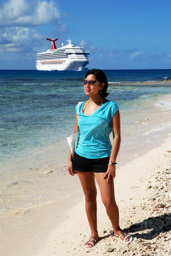 Cruising In Cayman Islands. The girl standing on Seven Mile beach with a cruise liner in a background (Grand Cayman, Cayman Islands royalty free stock photos