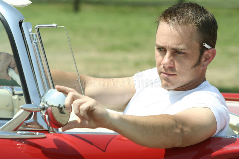 Cruising Greaser. A retro looking American man cruising in a vintage convertible car stock images