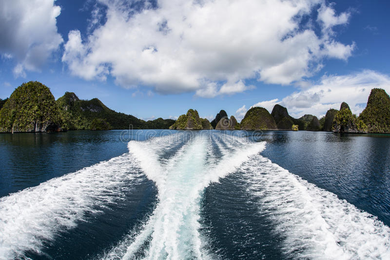 Cruising Through Limestone Islands in Raja Ampat. Beautiful scenery in Wayag, Raja Ampat, Indonesia. This remote region is known as the heart of the Coral stock photography