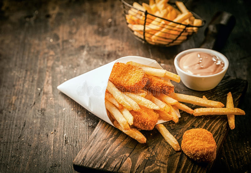 Crumbed fried fish nuggets with potato chips stock image