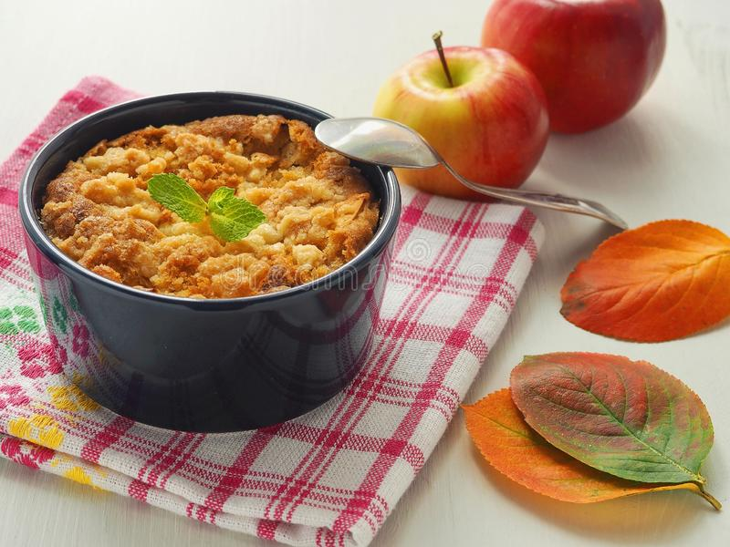 Crumble cake decorated with mint leaf, red apples and autumn leaves. Homemade pudding in a mug royalty free stock photos