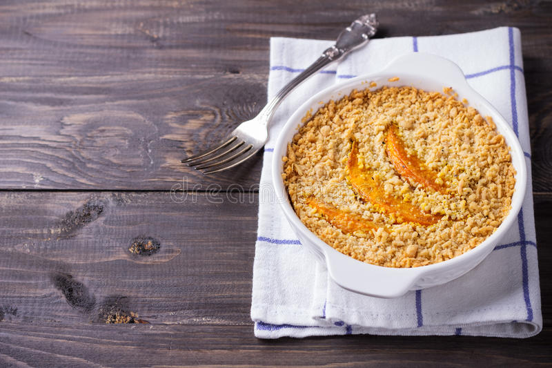Crumble with pumpkin and cheese. In white dish on the wooden table royalty free stock photos