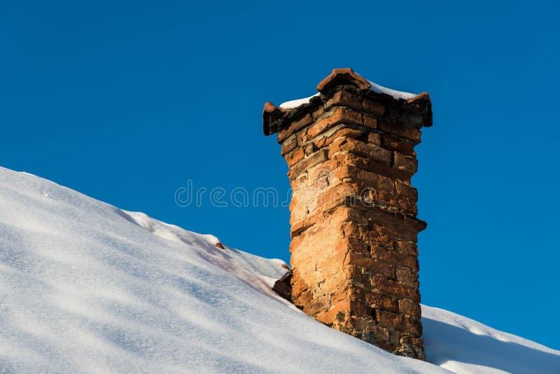 Crumbling old brick chimney on old abandoned house stock image