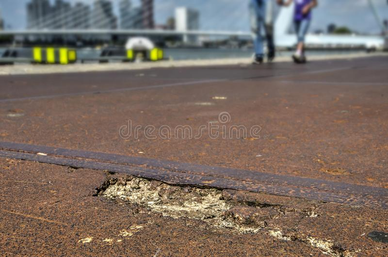 Crumbling quayside concrete. Damaged concrete of stelcon tiles on the quay of Wilhelminapier in Rotterdam, the Netherlands, with Erasmus Bridge blurred in the royalty free stock image
