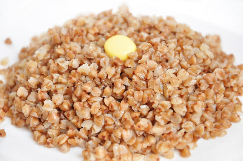Crumbly buckwheat with butter. Appetizing crumbly buckwheat with butter on white background stock image