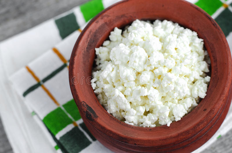 Crumbly homemade cottage cheese. In a clay pot royalty free stock photography