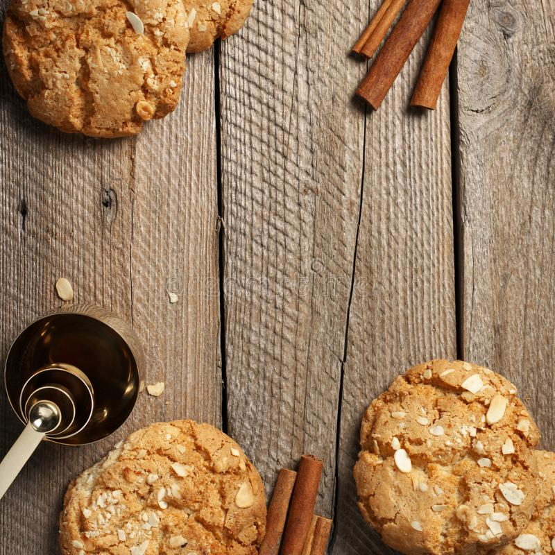 Crumbly peanut cookies on wood. Crumbly peanut cookies with cinnamon sticks and measuring spoon on rustic wooden background. Top view stock image