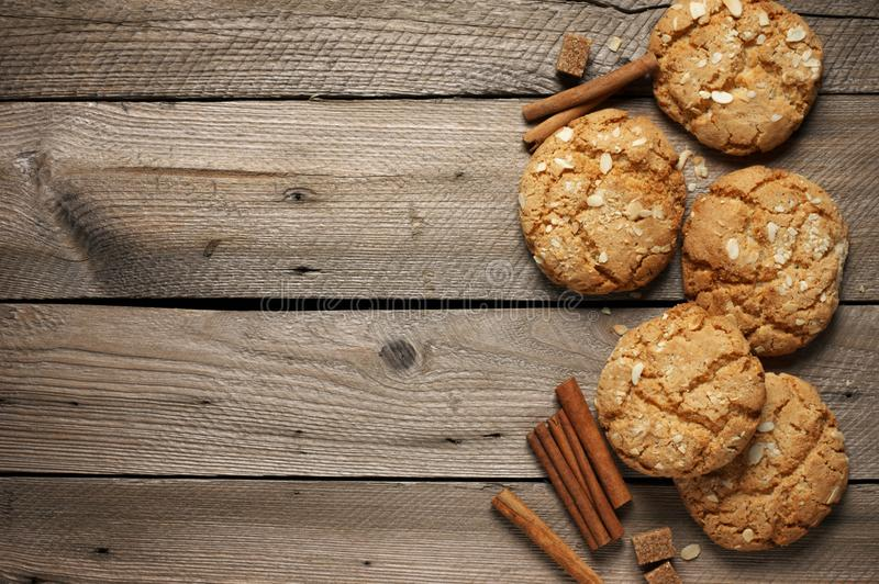 Crumbly peanut cookies on wood. Crumbly peanut cookies with cinnamon sticks on rustic wooden background. Top view royalty free stock photo