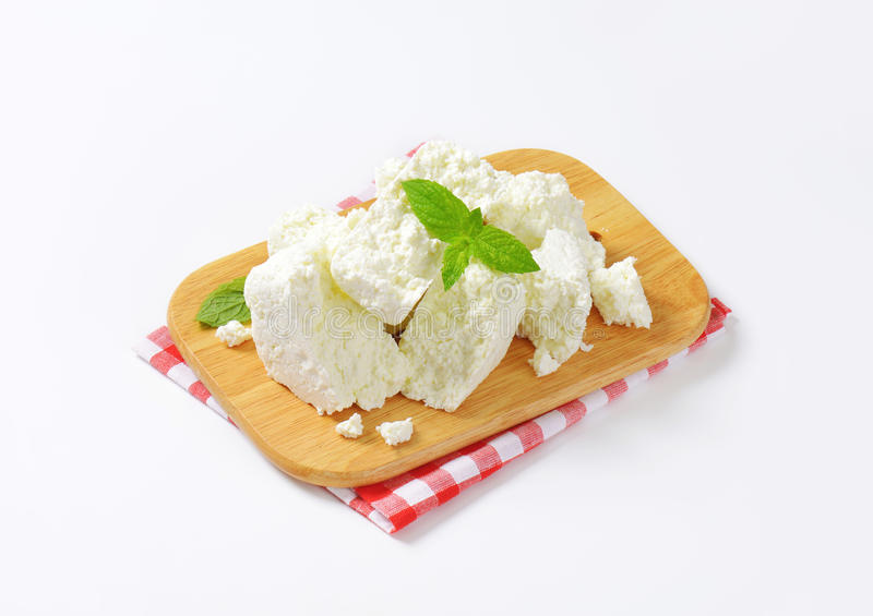 Crumbly white cheese. On cutting board stock images