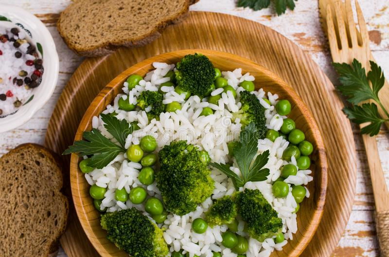 Crumbly white rice. With green vegetables in the dish on the table. Selective focus royalty free stock image