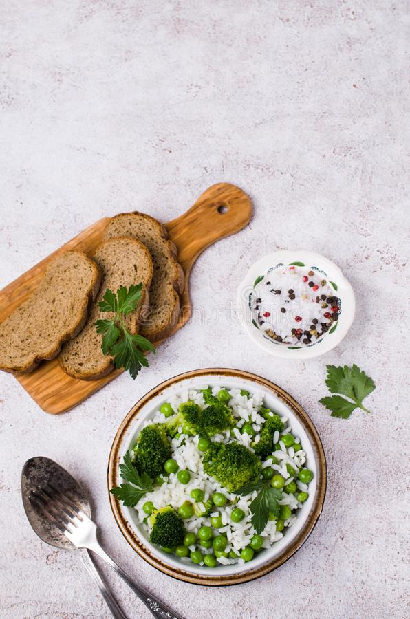 Crumbly white rice. With green vegetables in the dish on the table. Selective focus stock photography