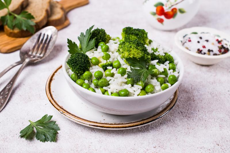 Crumbly white rice. With green vegetables in the dish on the table. Selective focus stock image