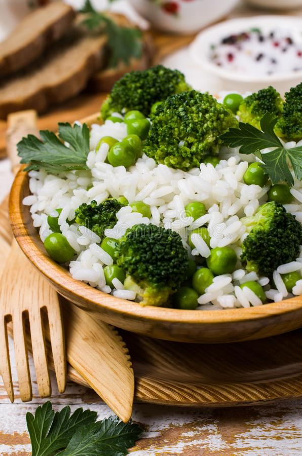 Crumbly white rice. With green vegetables in the dish on the table. Selective focus stock photo