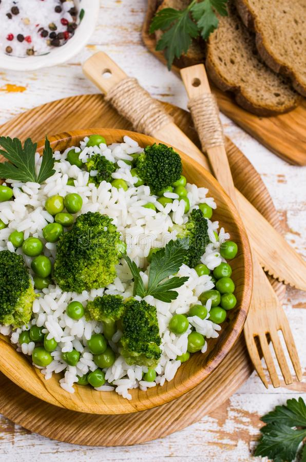 Crumbly white rice. With green vegetables in the dish on the table. Selective focus stock images