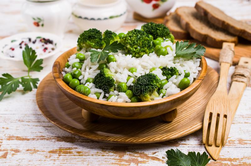 Crumbly white rice. With green vegetables in the dish on the table. Selective focus stock photos